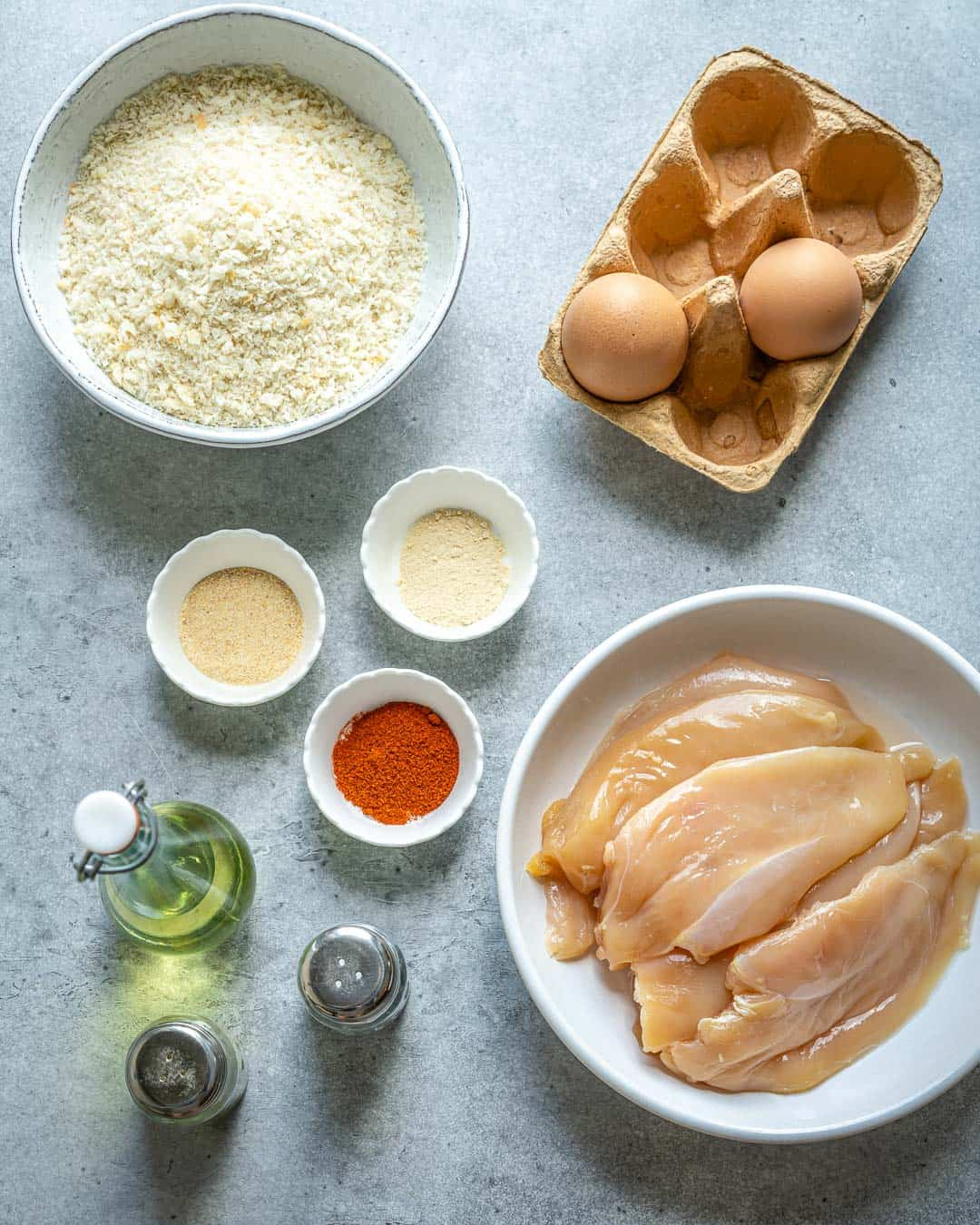 Ingredients for chicken nuggets on gray counter.