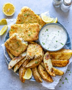 top view air fried fish with potato wedges and white dip