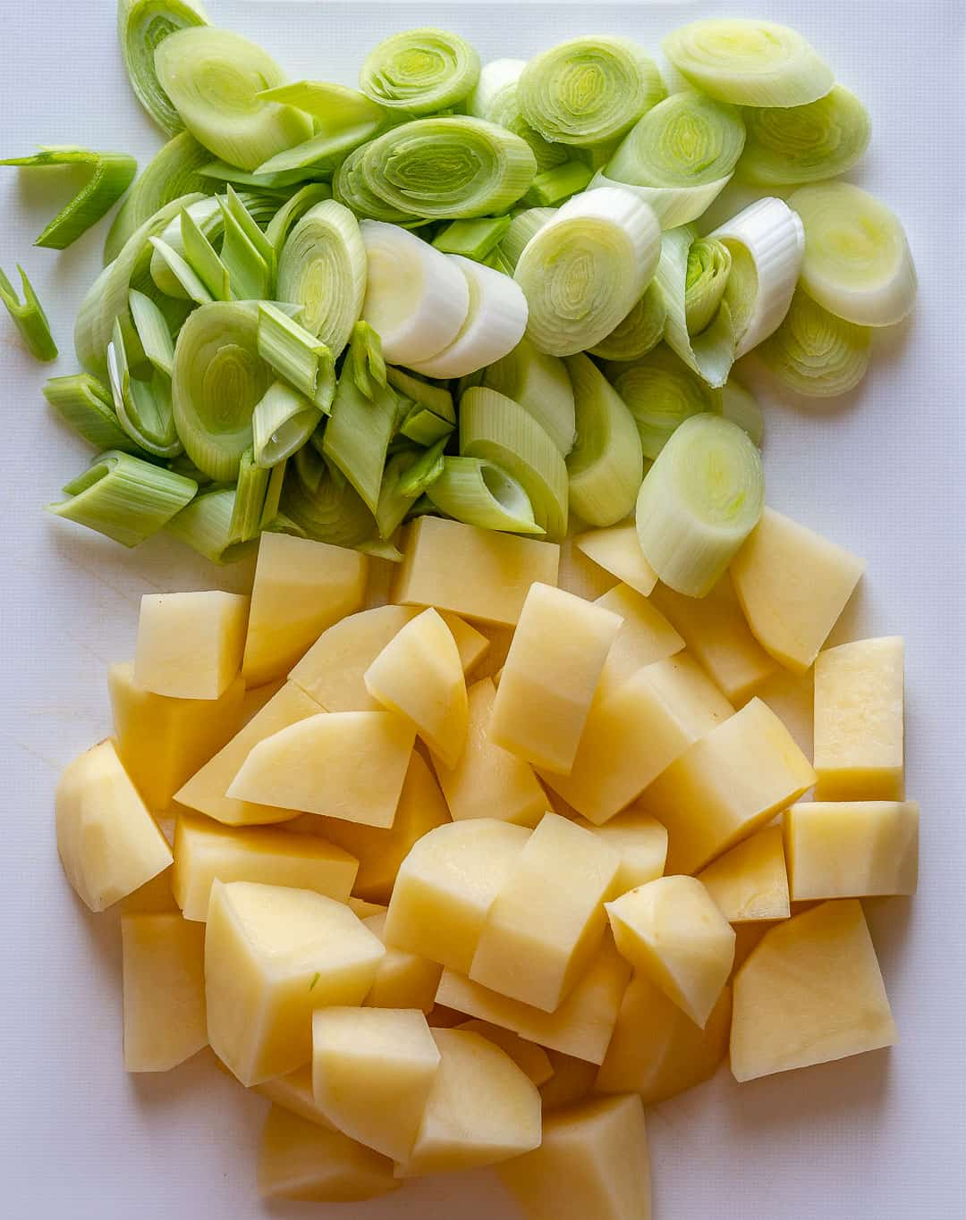Chopped leeks and potatoes on a cutting board