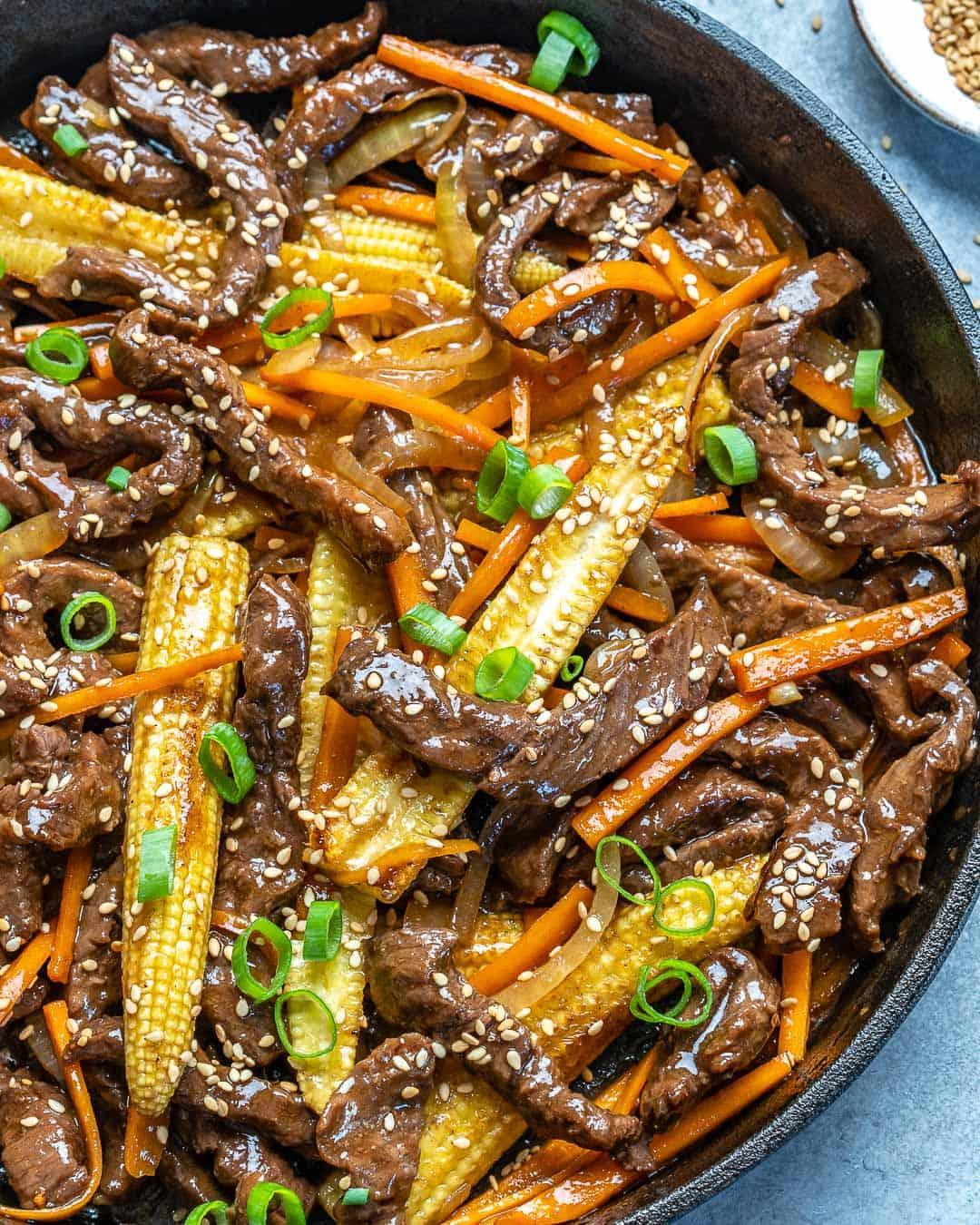 Beef stir fry in a black skillet.