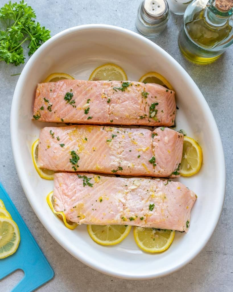 raw marinated salmon in a white dish ready to be baked