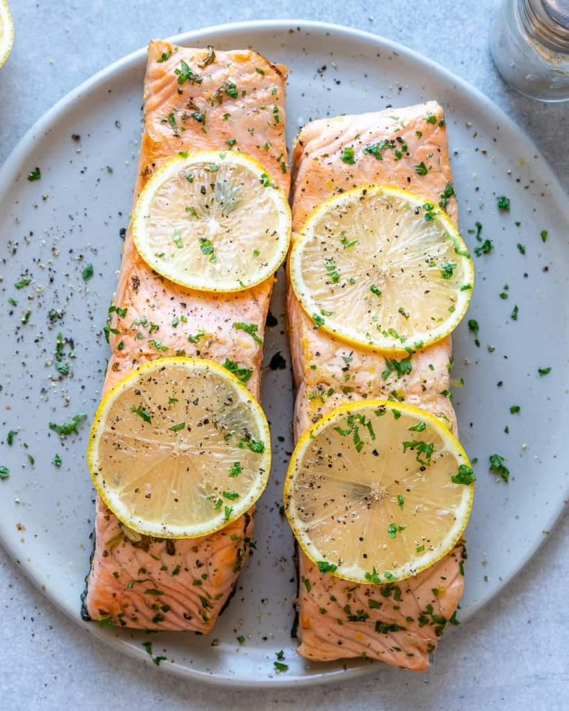 top view salmon with sliced lemon garnishes