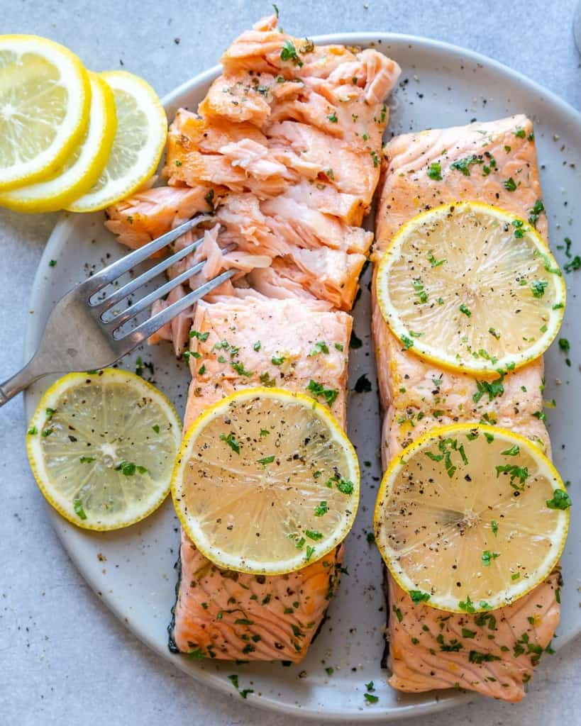 top view of fork flaking baked salmon on a white plate