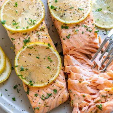 two baked salmon on plate with fork flaking it