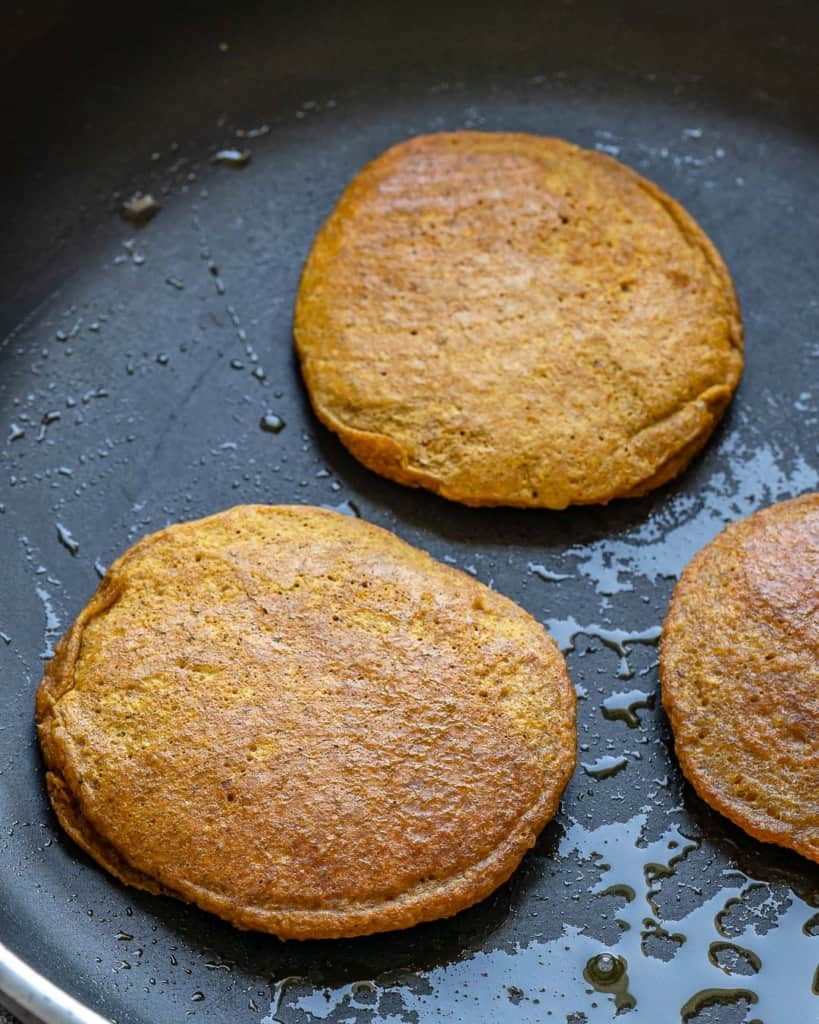 pancakes being cooked in black pan