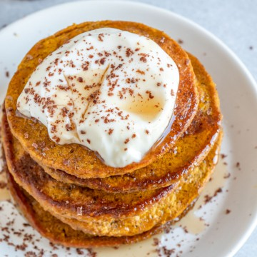 top view of pumpkin pancakes topped with yogurt maple syrup and cinnamon
