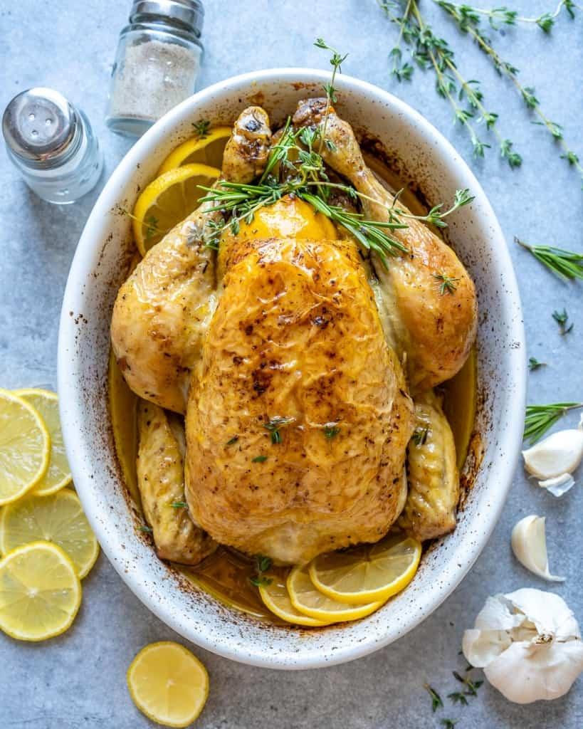 top view roast chicken in white baking dish and lemon granish