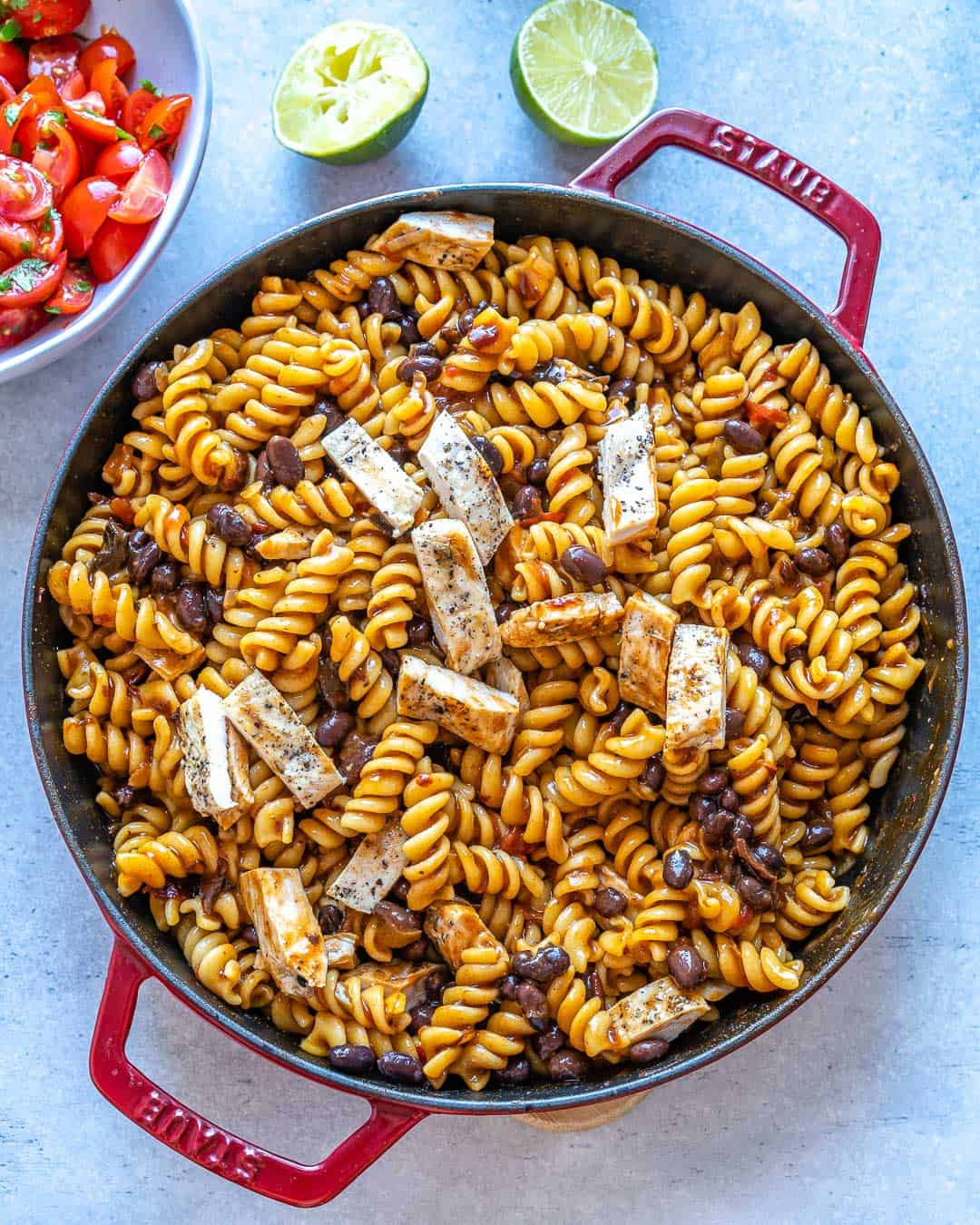 Grilled chicken added to pot of pasta.
