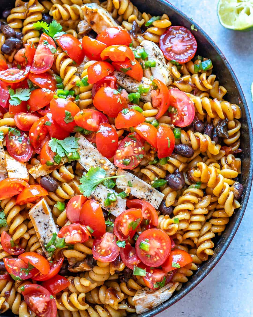 Partial pot of Mexican Chipotle Pasta with tomatoes and cilantro on top