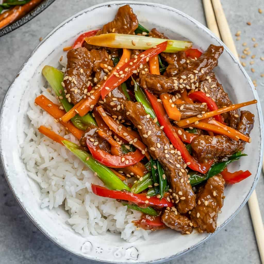 mongolian beef with rice in a white bowl