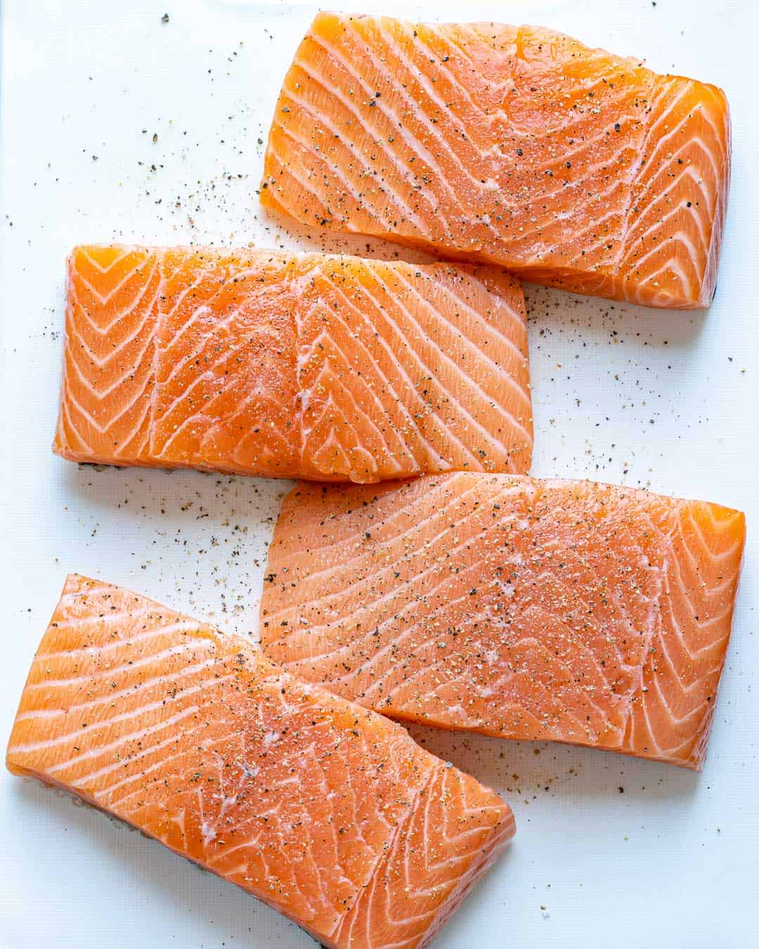 Four salmon filets seasoned with salt and pepper