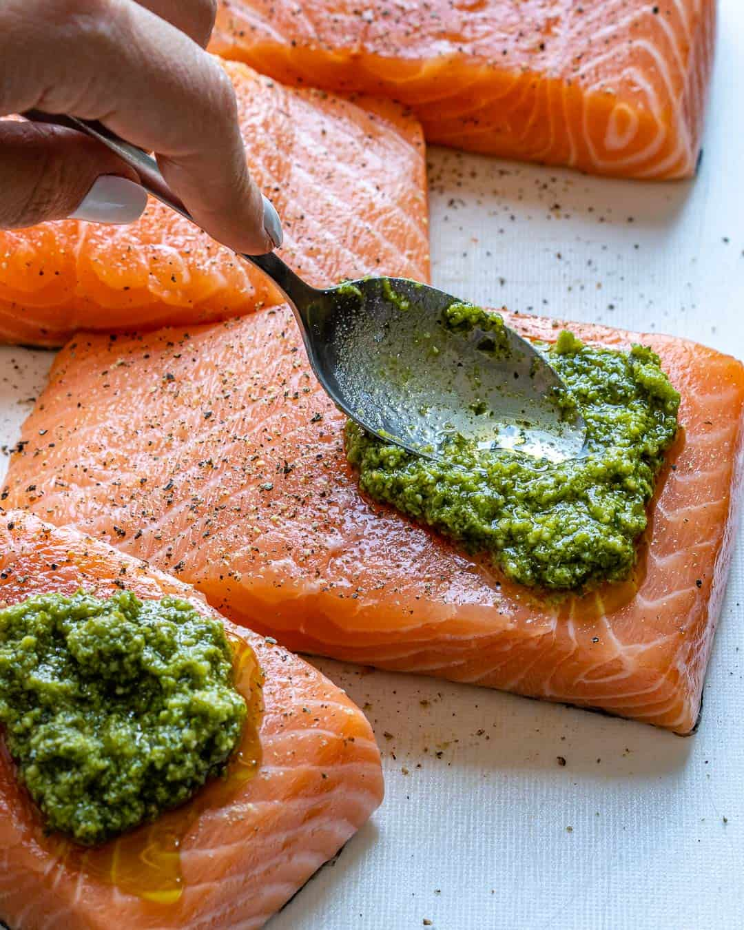 Spoon spreading pesto sauce evenly on salmon fillets