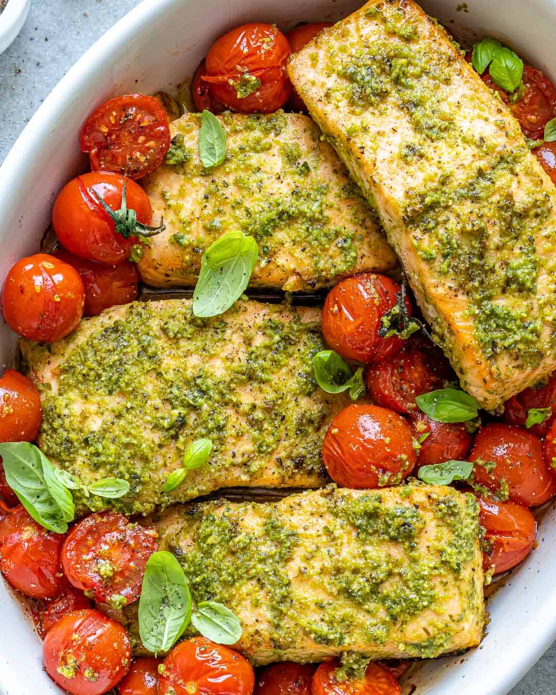 Baked Pesto Salmon in white serving dish with cherry tomatoes