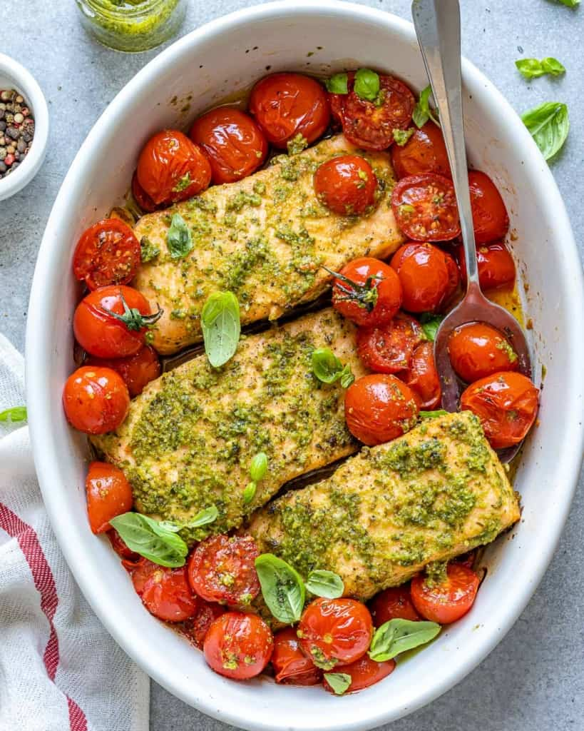 top view of spoon in baked salmon and tomatoes