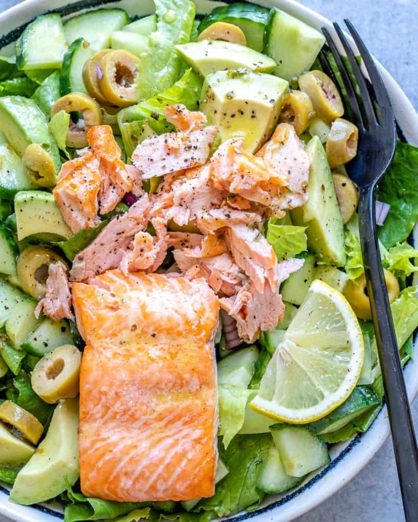 close up view of seared salmon over salad