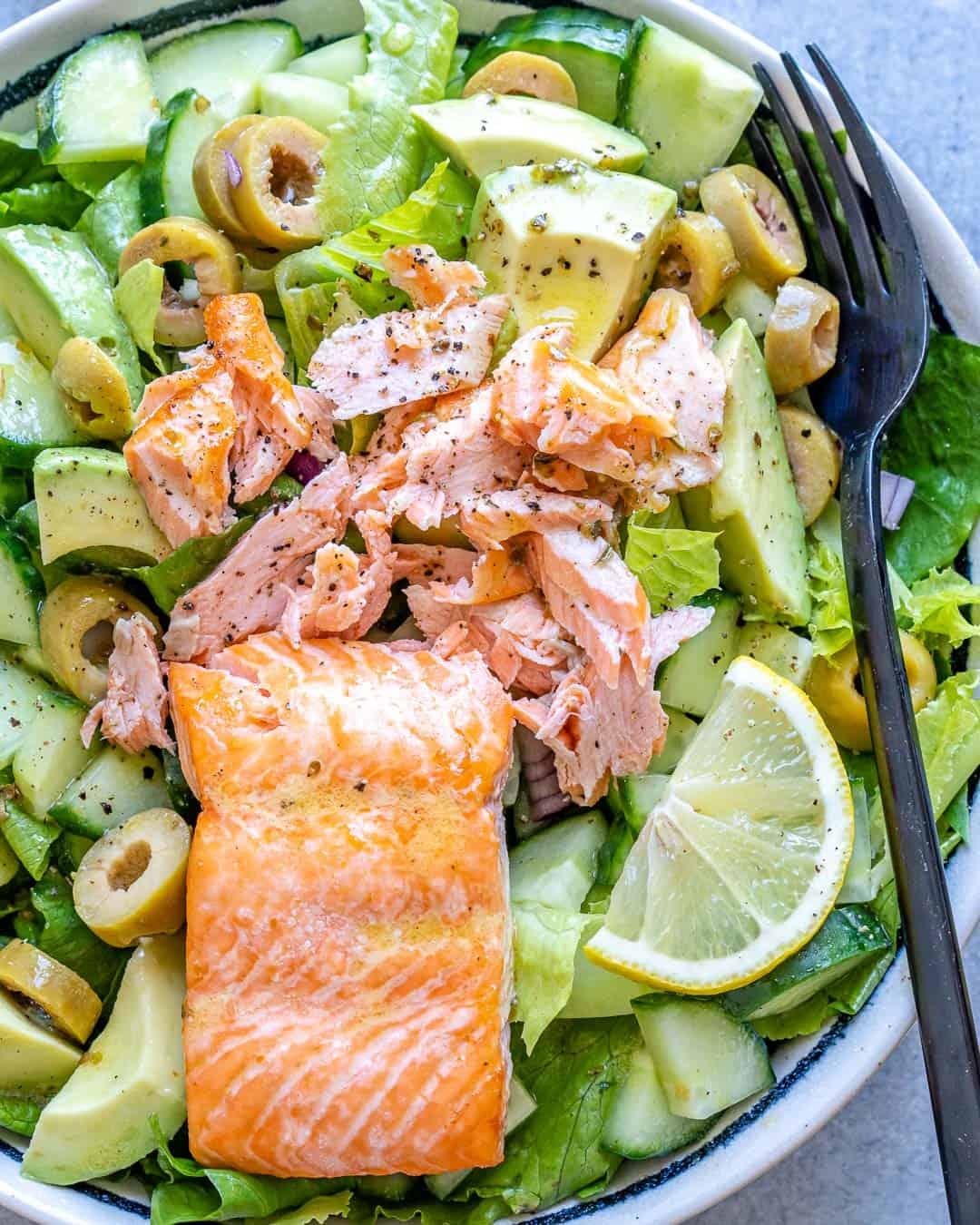 Full bowl of salad with flaky salmon and black fork on top