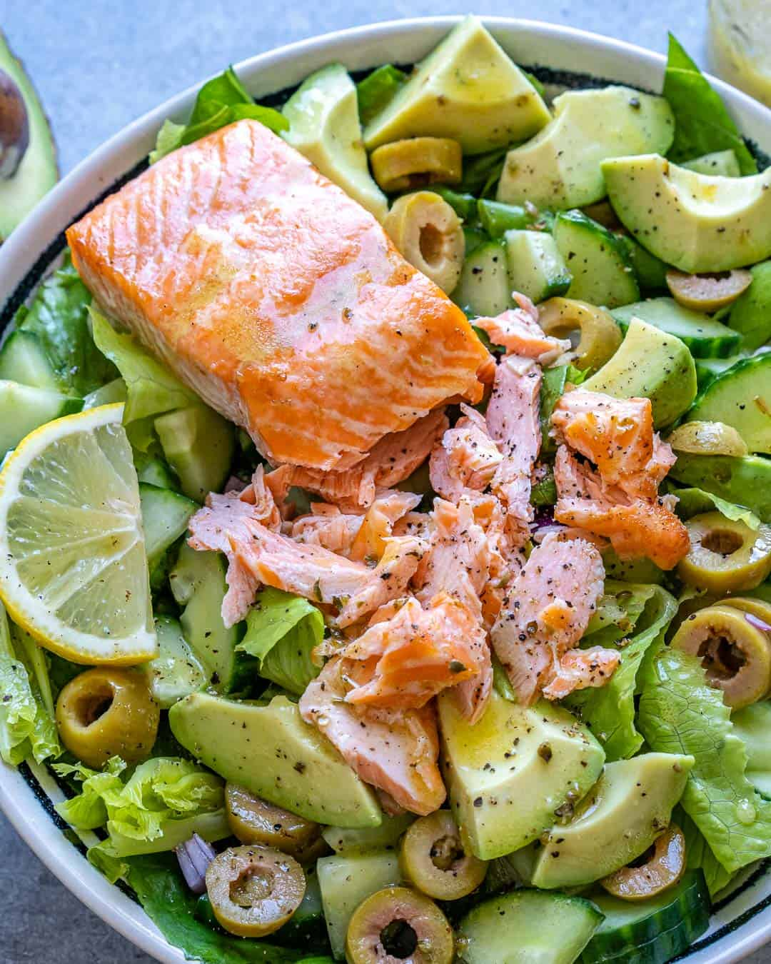 Salmon avocado salad in a bowl with shredded salmon and dressing