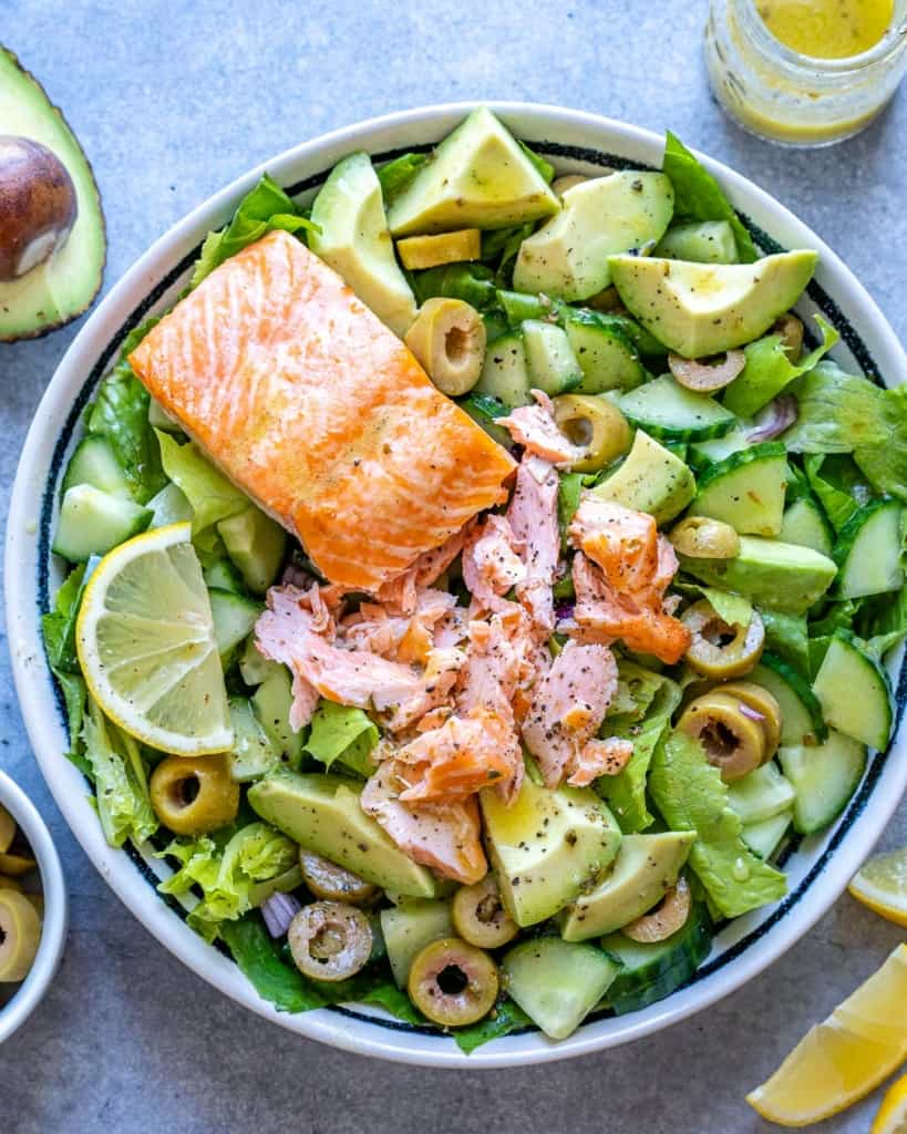 top view of flaked salmon over green salad
