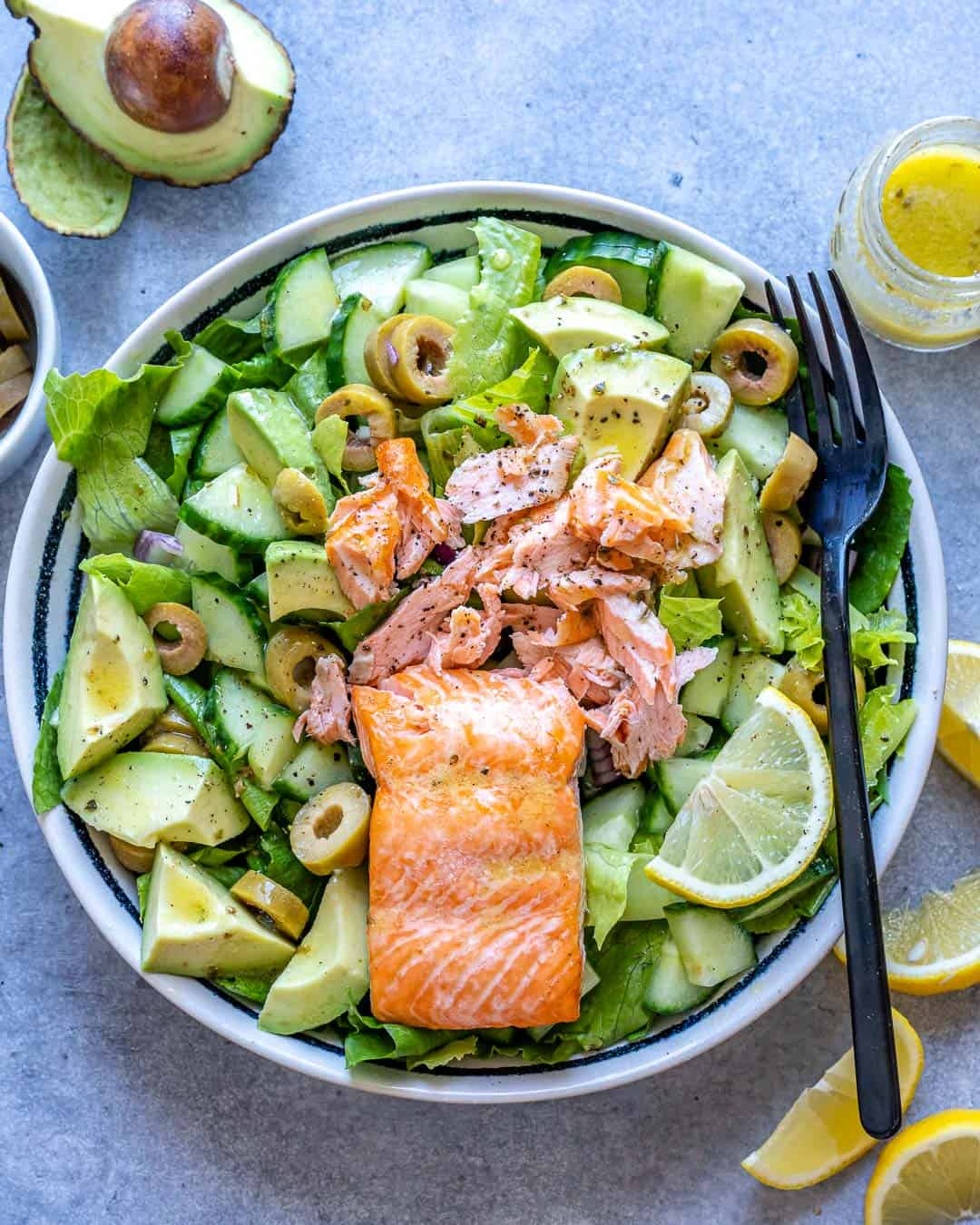 Top view of white bowl with salmon avocado salad and lemon wedges on the side