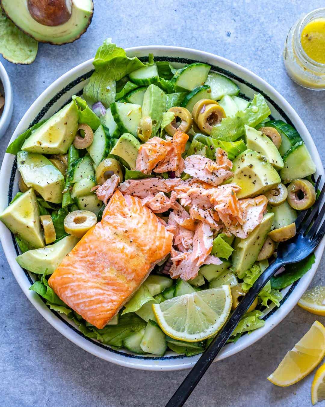salmon topped over salad bowl