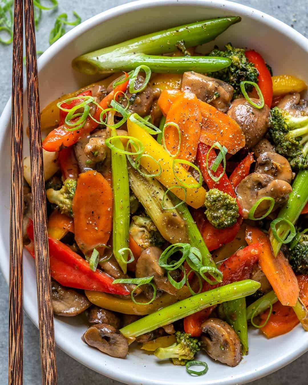 Sweet & sour vegetable stir fry in white bowl with chopsticks.