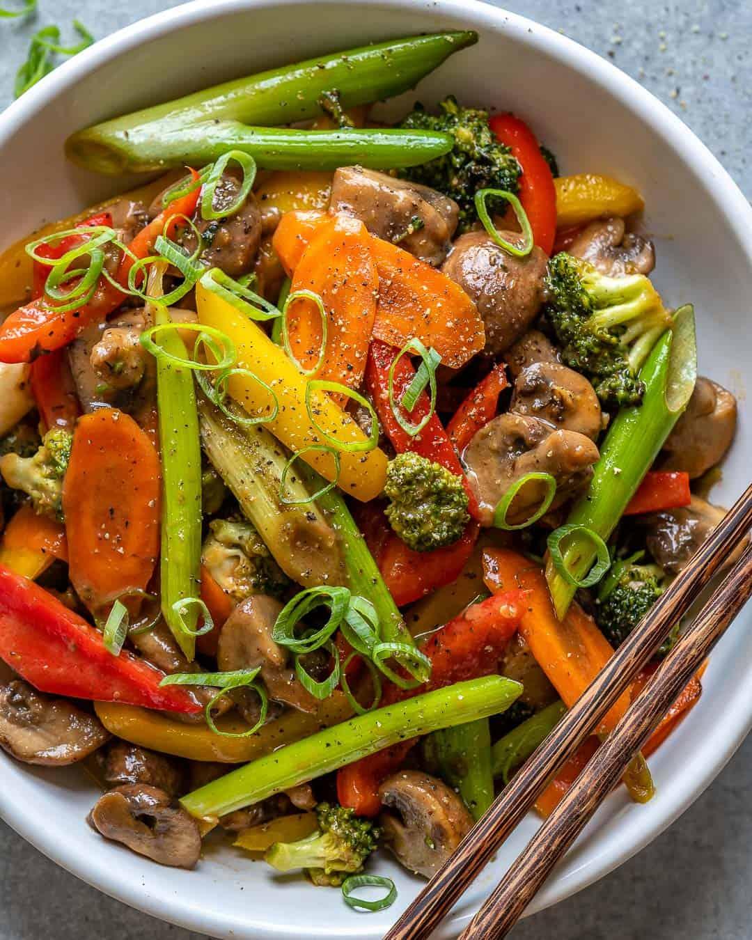 White bowl of vegetable stir fry with chopsticks.