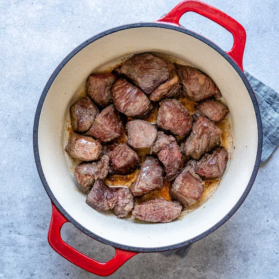 Chunks of steak cooking in dutch oven for soup