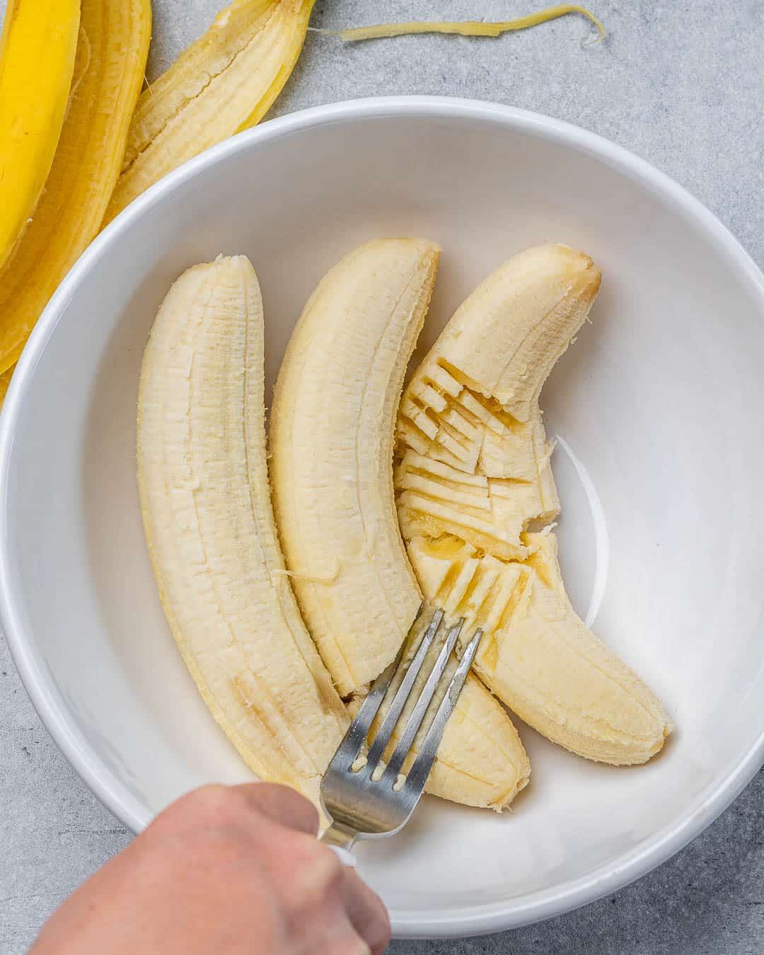 Fork mashing ripe bananas in white bowl
