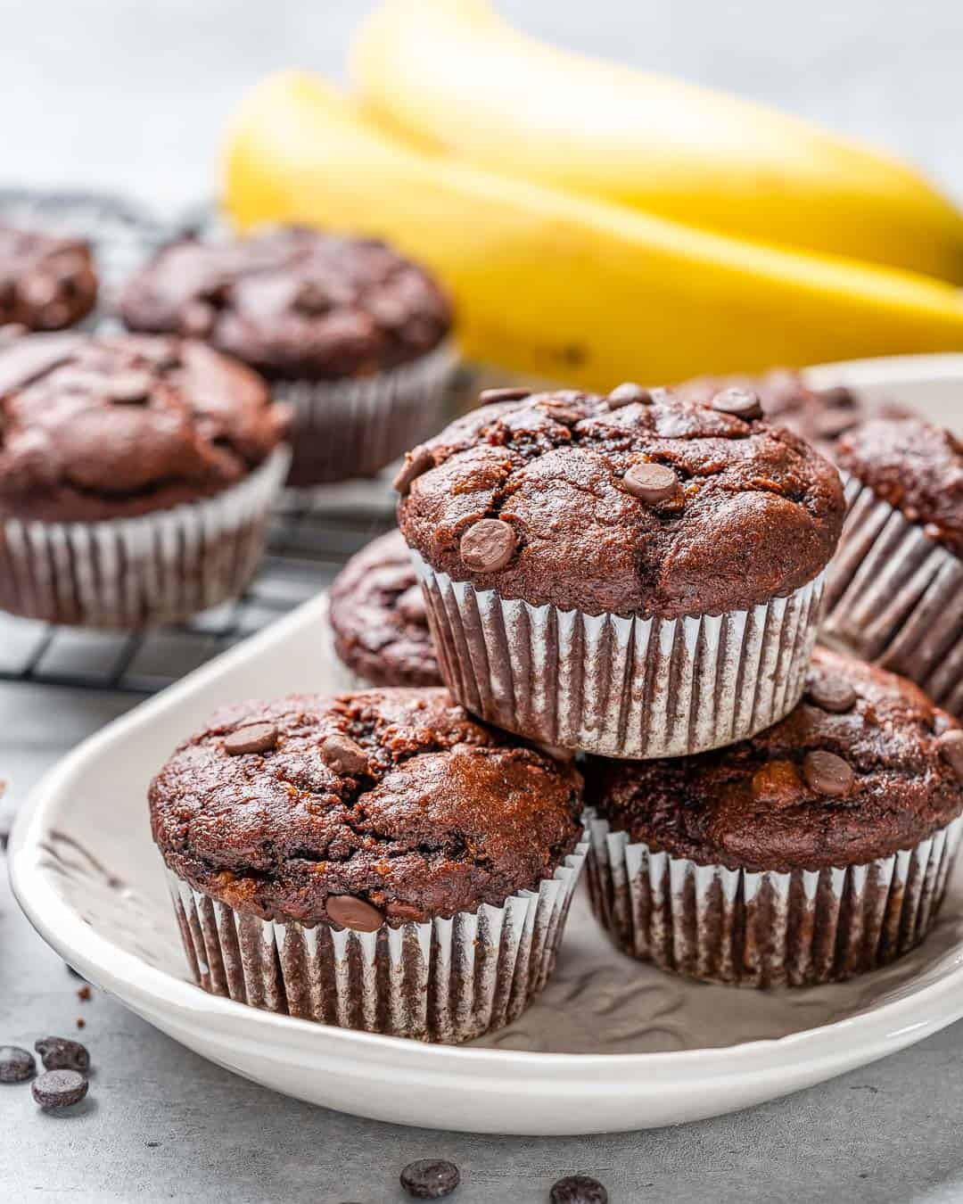 White tray of healthy chocolate peanut butter banana muffins with bananas in background
