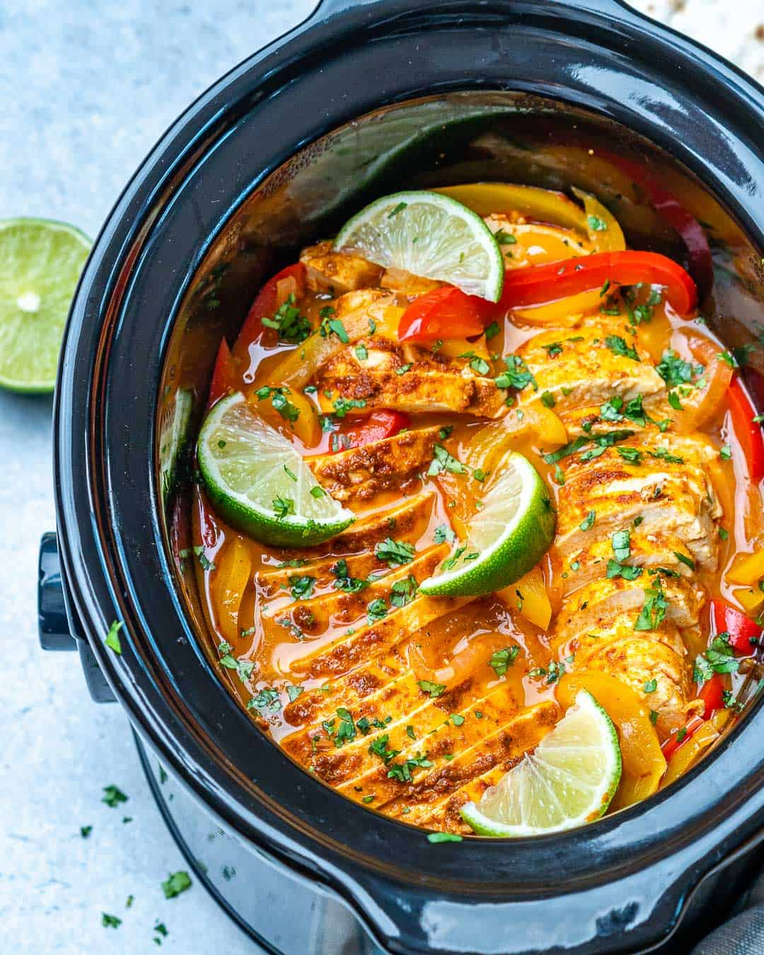 Slow cooker chicken fajitas in black Crockpot with limes and cilantro garnishes.