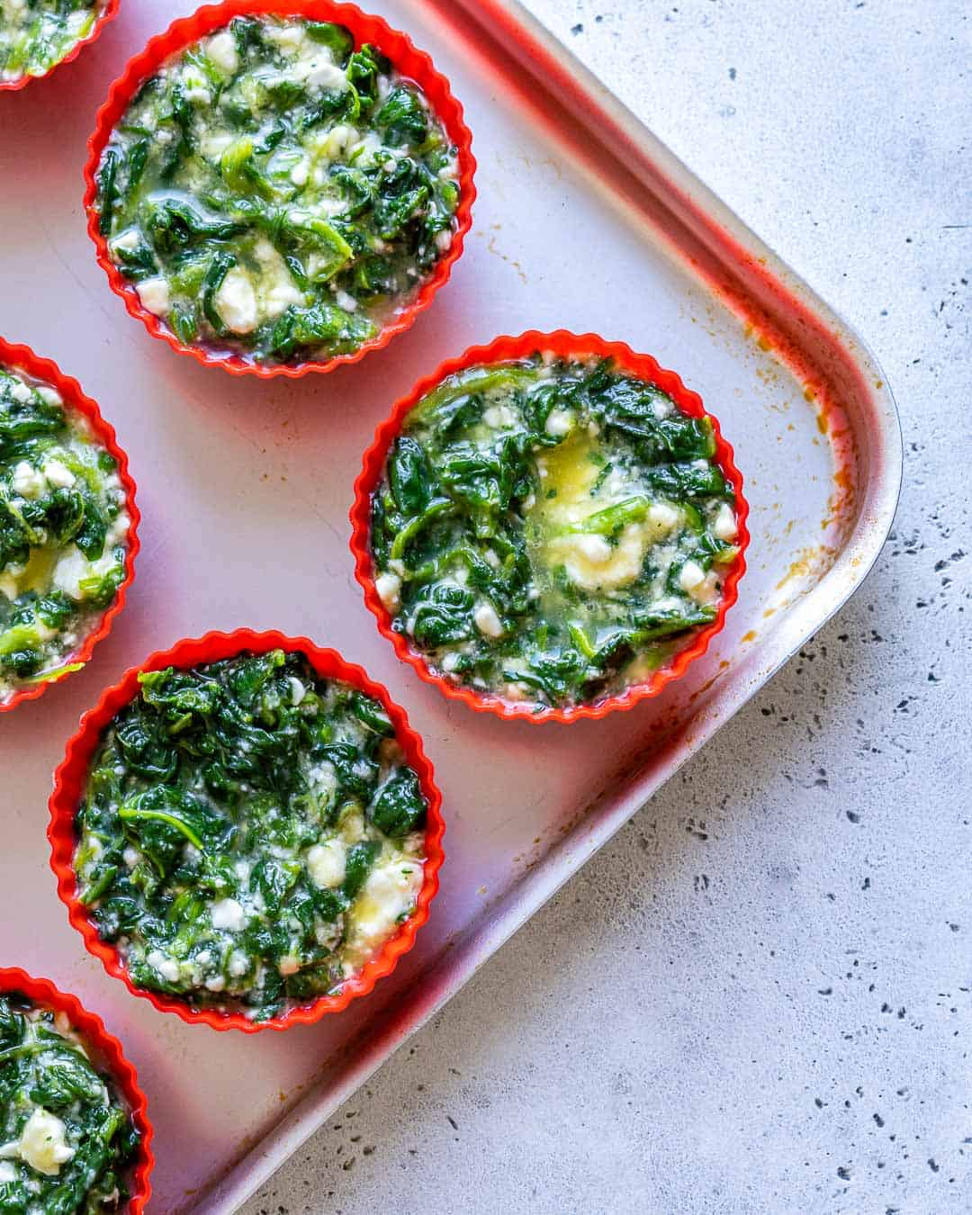 Muffin tin lined and filled with egg mixture.