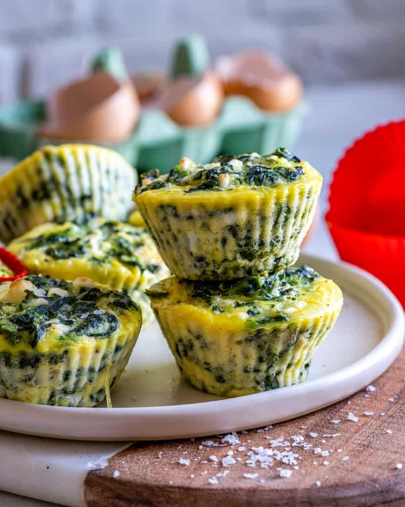 Stacked spinach and feta egg cups on white plate with eggs in background