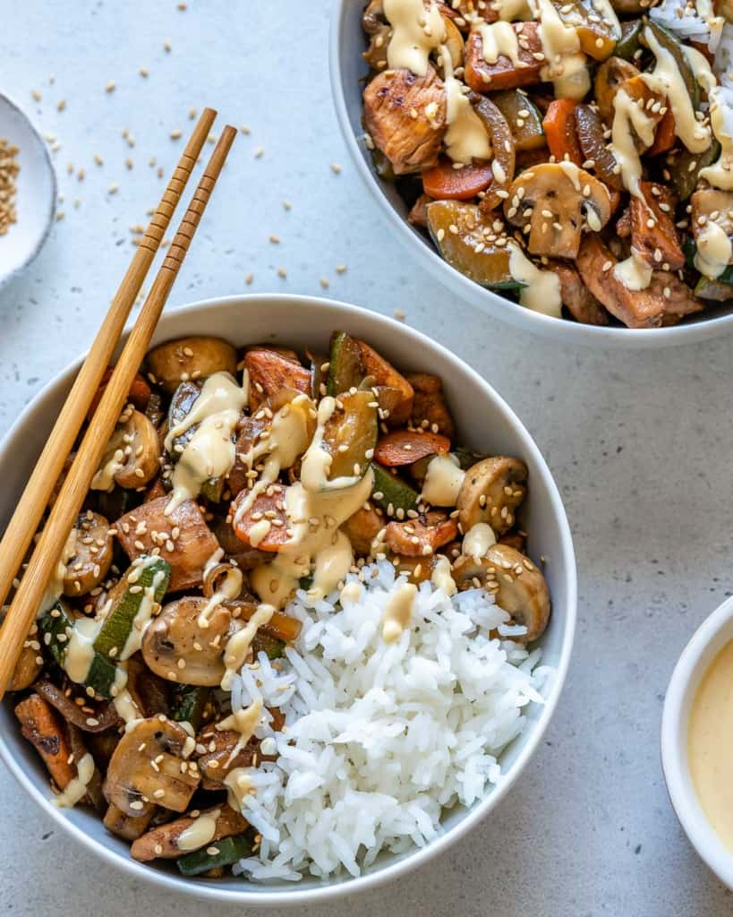 top view hibachi chicken bowl with white rice and chop sticks on the side