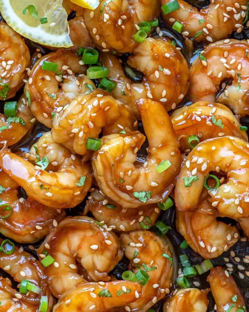 close up honey shrimp garnished with sesame, green onion, and lemon wedges