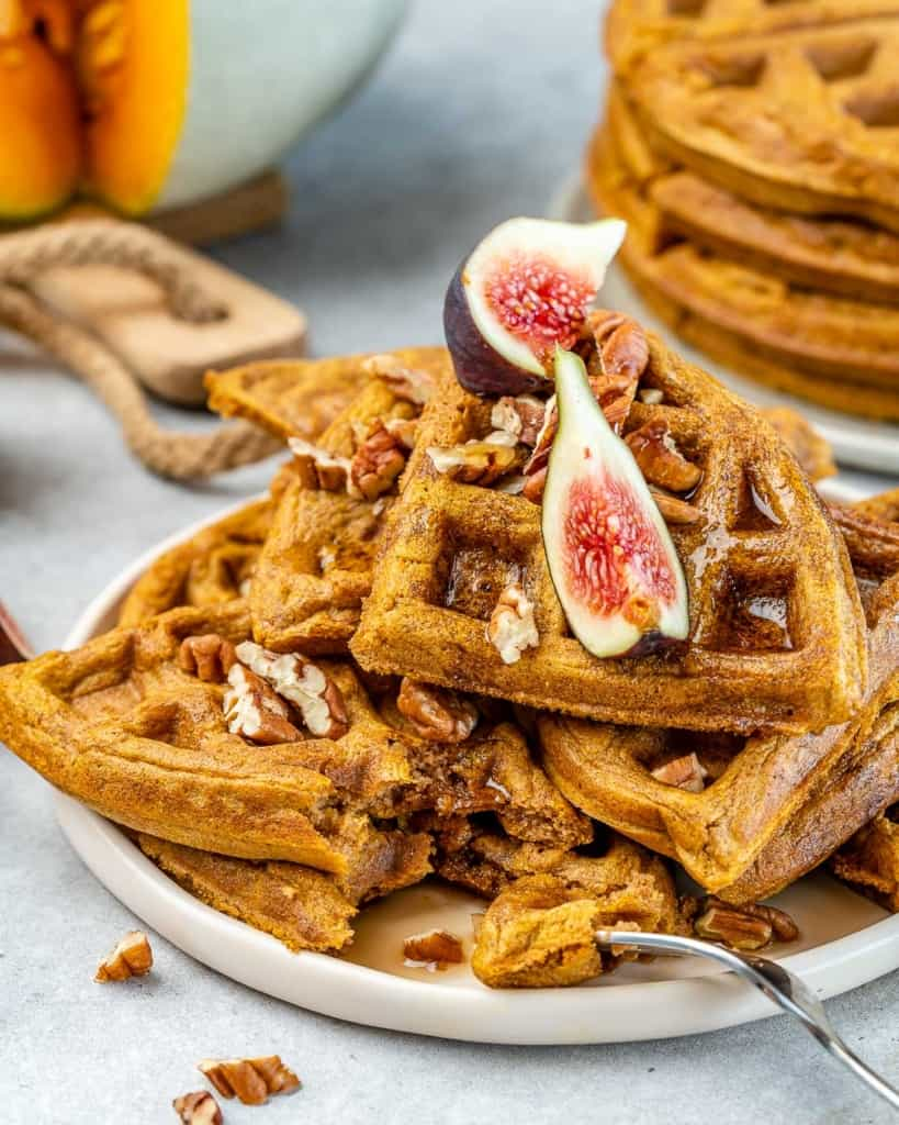 side shot of pumpkin waffles on a white plate