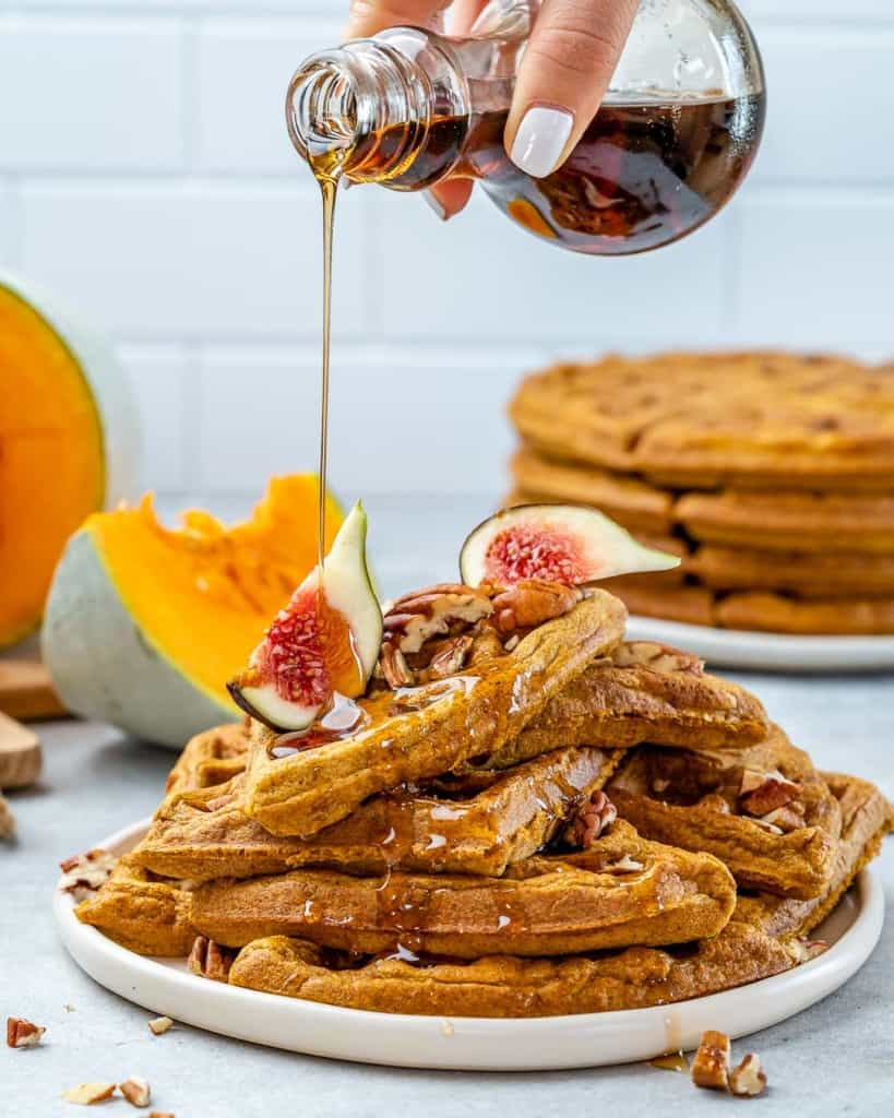 hand pouring maple syrup over waffles