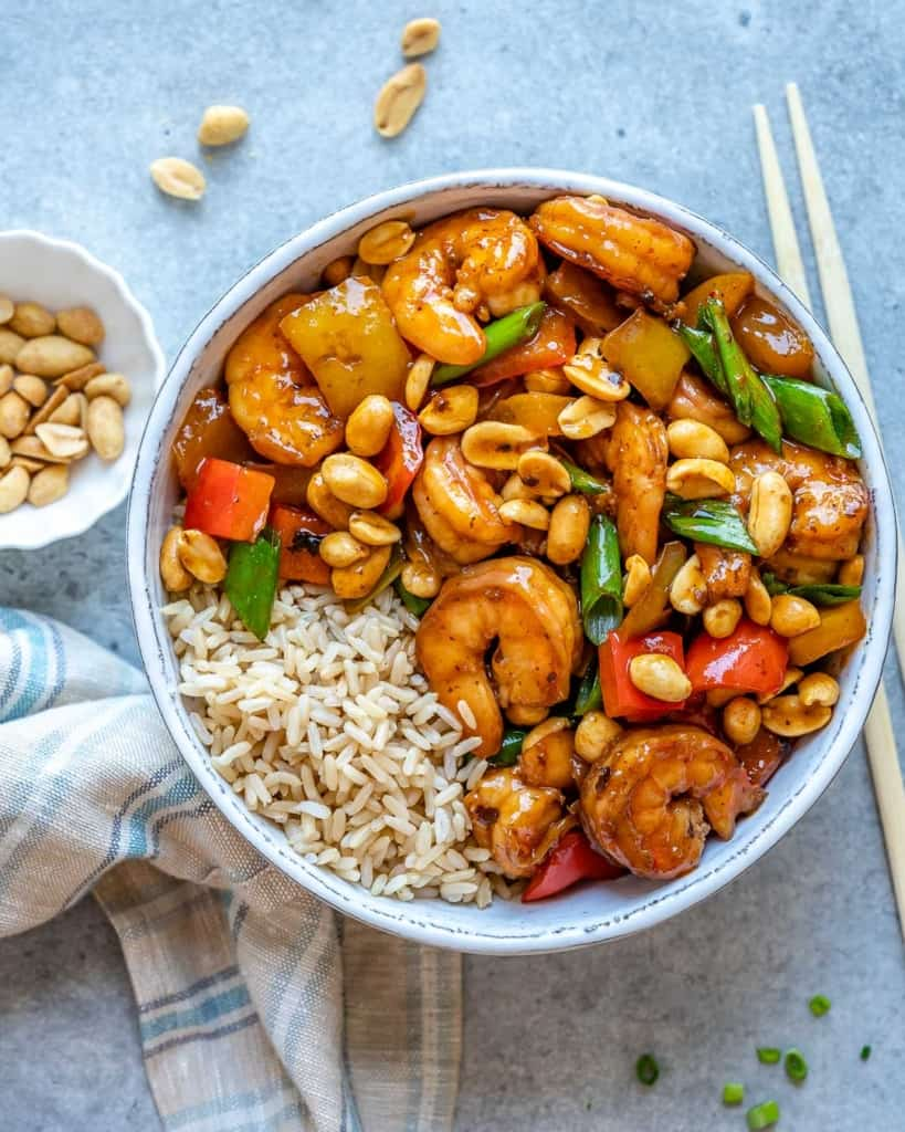 Top view of kung pao shrimp in white bowl with chop sticks