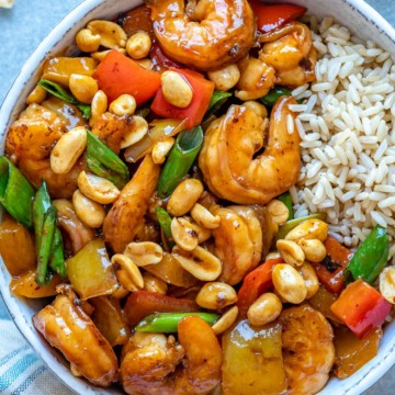 top view of kung pao shrimp in white bowl with brown rice
