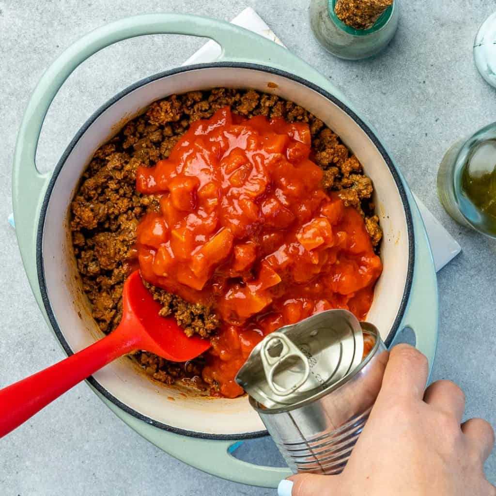 Diced tomatoes and ground beef in a blue pot.