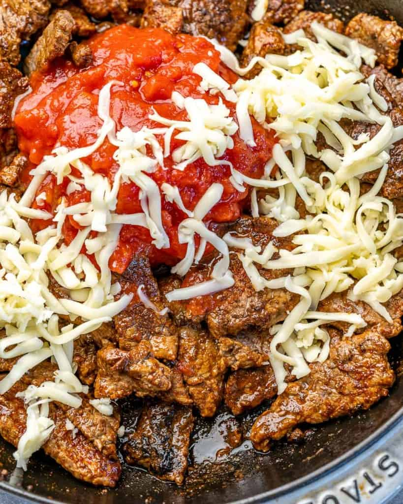 Overhead view of steak, shredded cheese and diced tomatoes in a skillet.