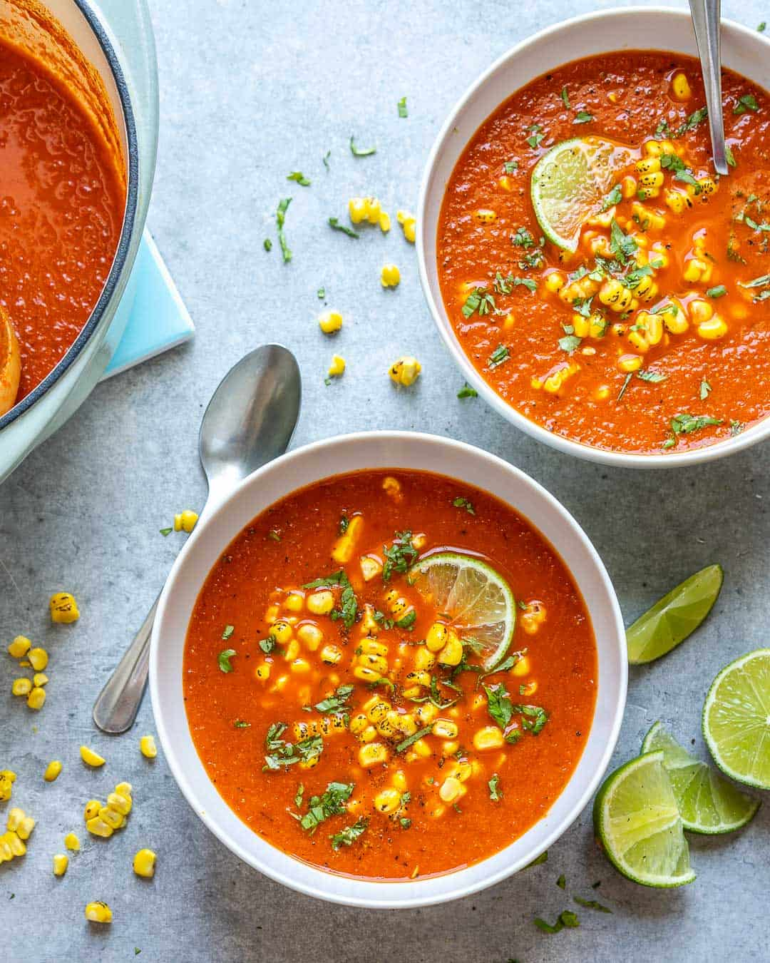 two bowls of Mexican sweet corn soup recipe with spoons and lime wedges