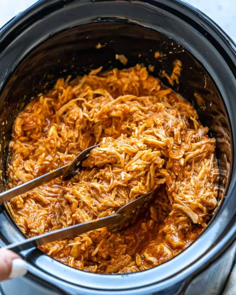 Top view of Crockpot filled with pulled chicken and tongs