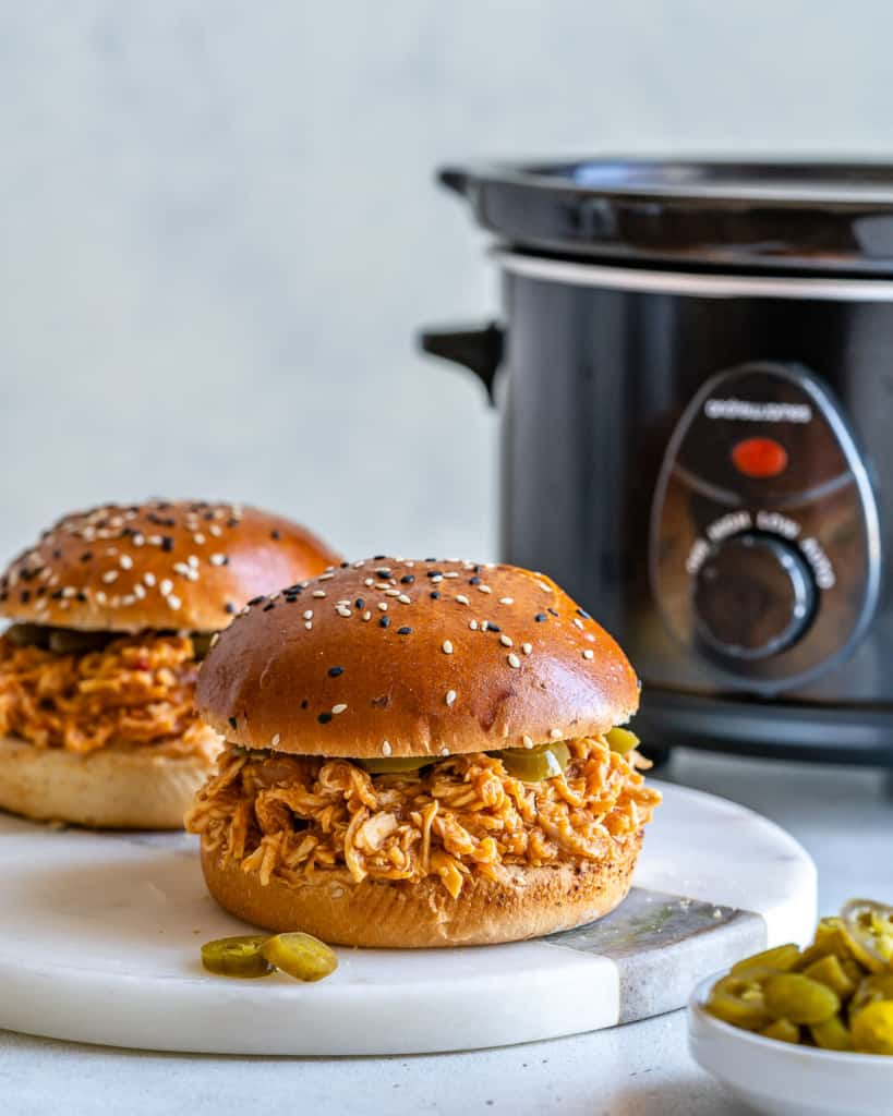 Two pulled chicken burgers with slow cooker in the background