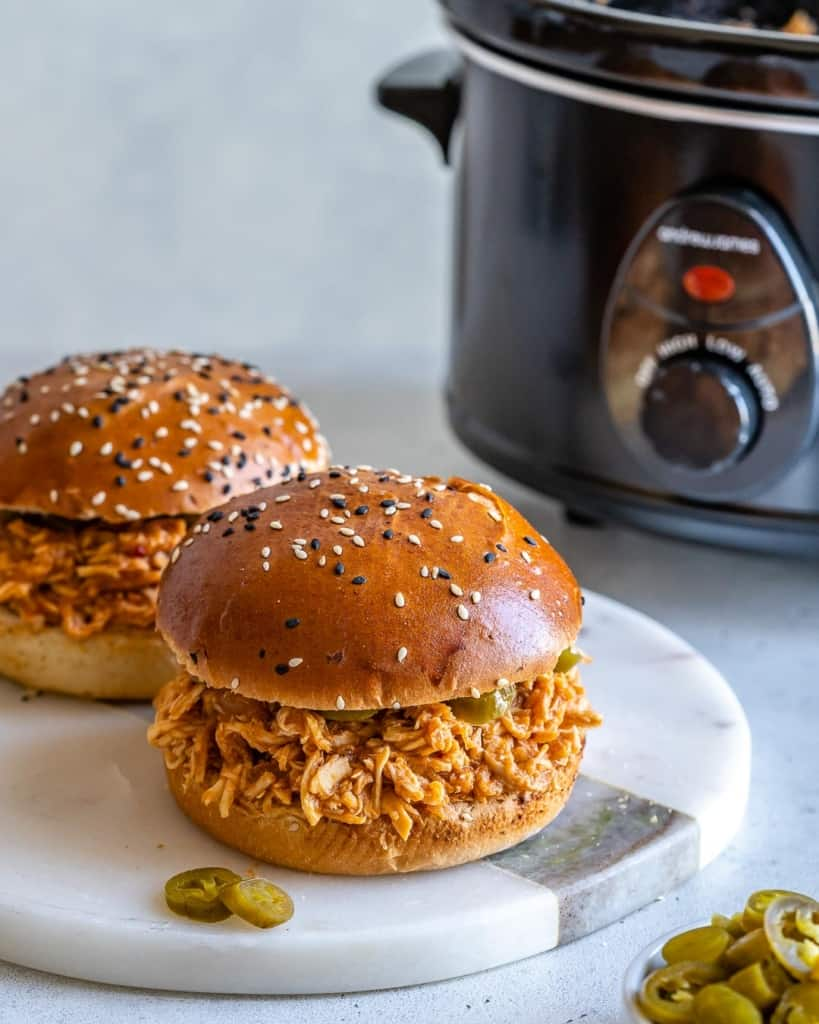 Two chicken burgers on white surface