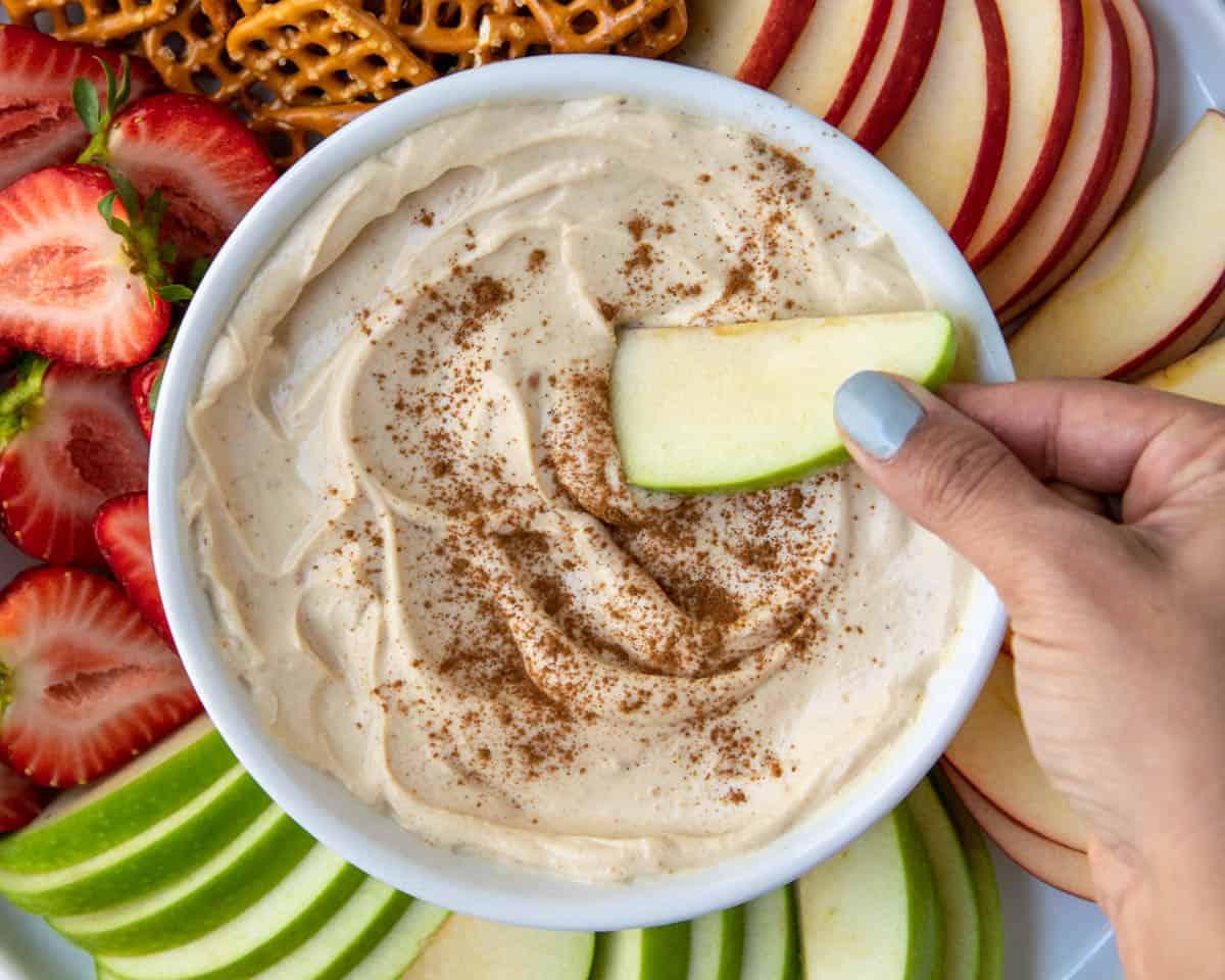 top view hand hold apple slice in yogurt fruit dip