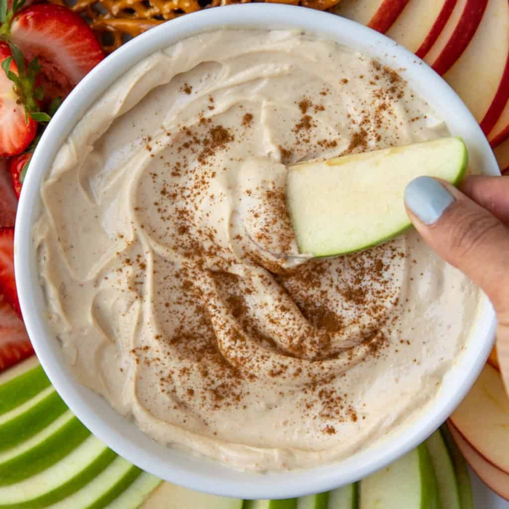 close up fruits bowl with hand holding apple in dip