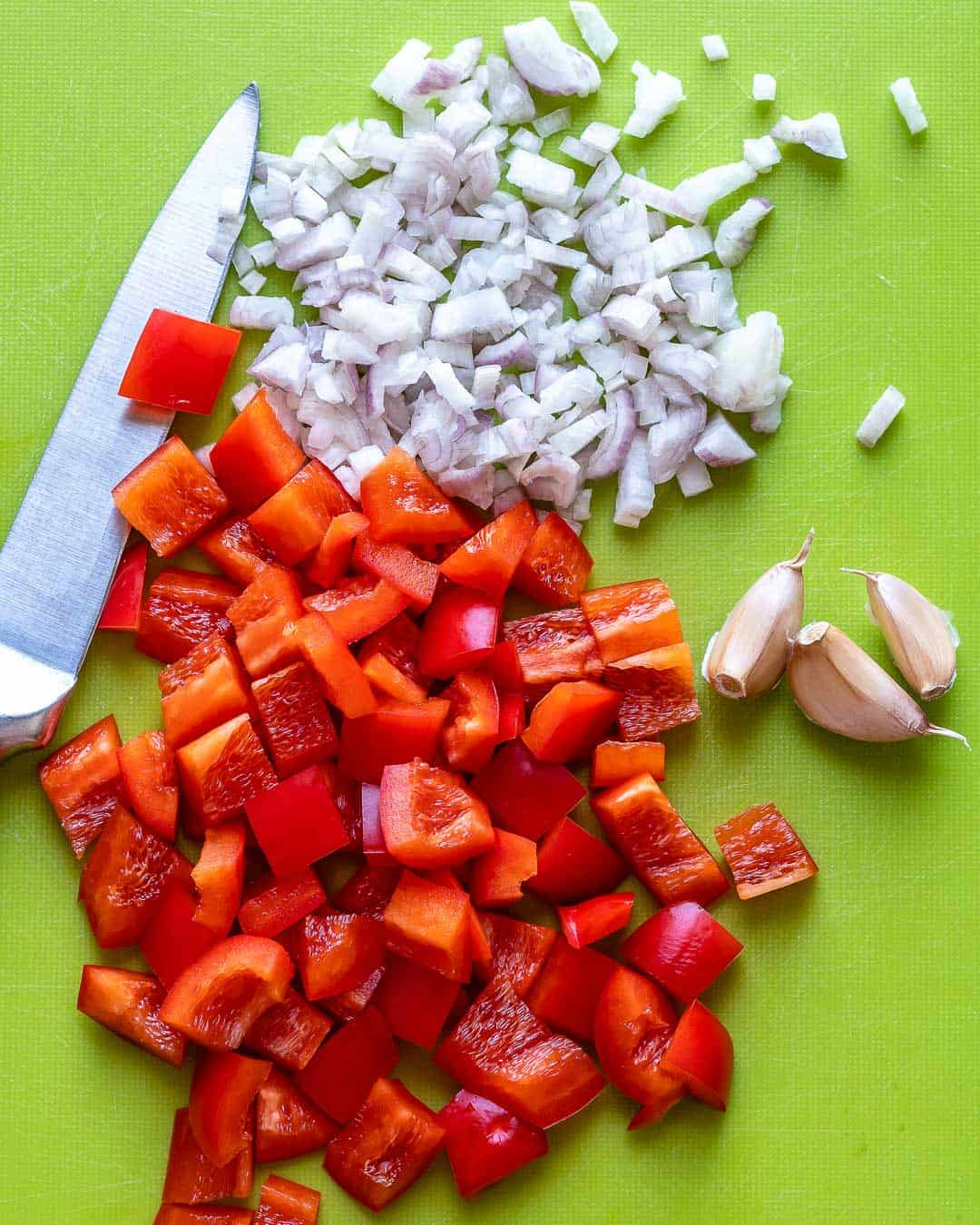 Chopped shallots and bell pepper on cutting board