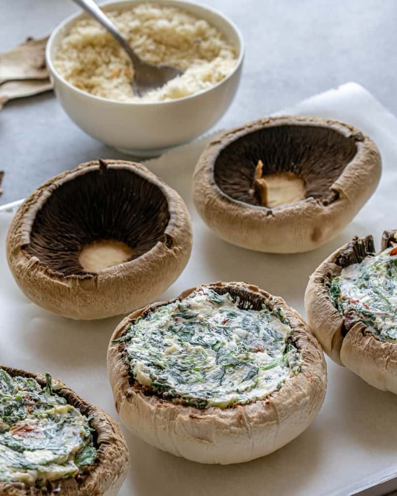 Filling up mushrooms with stuffing.