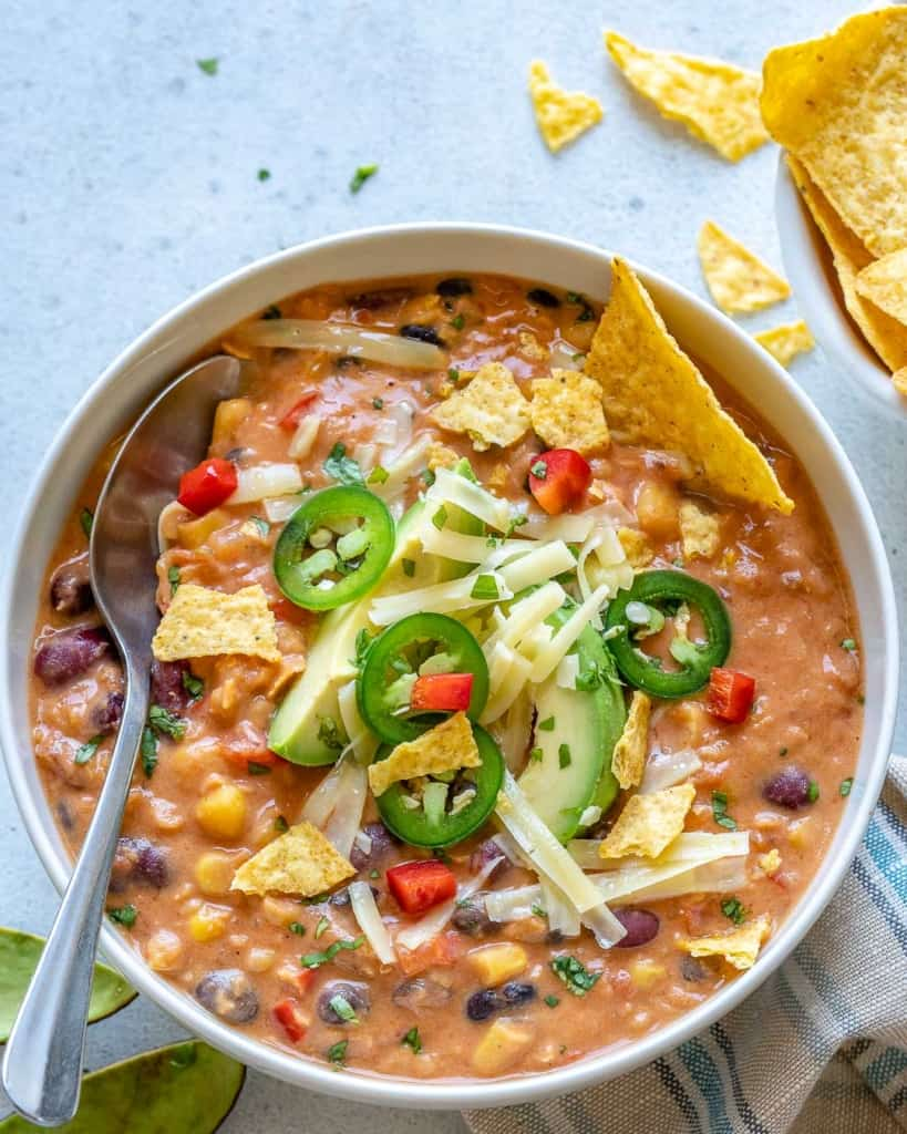 spoon in the bowl of tortilla soup with toppings