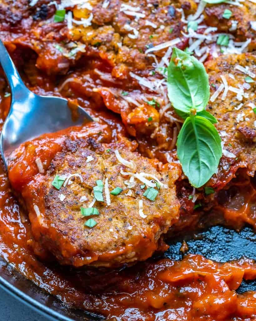 A close up shot of a meatball on a spoon.